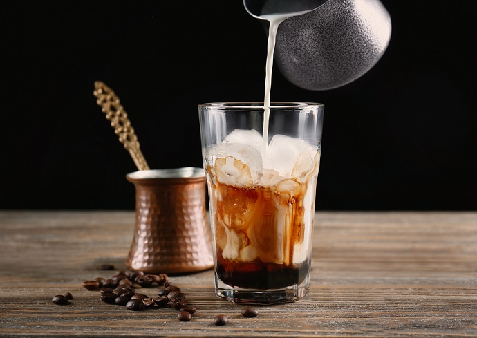 Pouring-milk-into-glass-with-iced-coffee