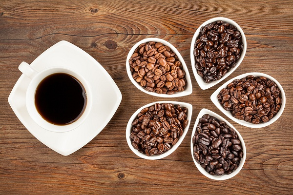 Image of a cup of coffee and five containers with coffee beans of varying darkness. Image used in Fourth Estate's article on roasting of coffee beans.