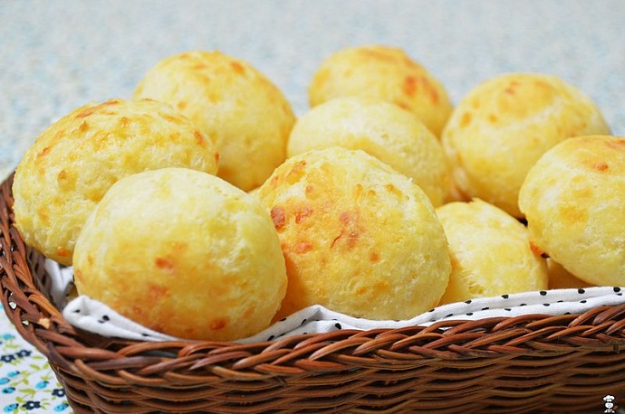Learn about gluten free bread and baking it with Fourth Estate's Pão-De-Queijo recipe. Image is a basket of cheesy rolls.